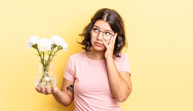 피곤한 후 지루하고 좌절하고 졸린 젊은 히스패닉 여성. 꽃 냄비 개념