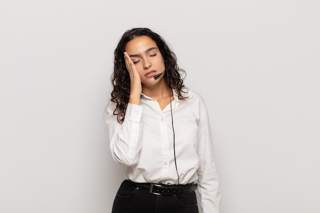 Young hispanic woman feeling bored, frustrated and sleepy after a tiresome, dull and tedious task, holding face with hand