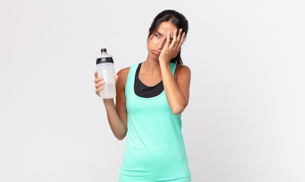 Young hispanic woman feeling bored, frustrated and sleepy after a tiresome and holding a water bottle. fitness concept