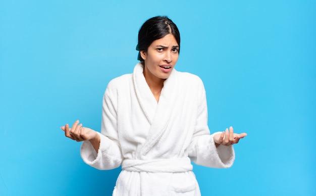 ヒスパニック系の若い女性は、無知で混乱していると感じ、どちらの選択肢や選択肢を選ぶべきかわからず、疑問に思っています。バスローブのコンセプト
