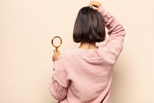 젊은 히스패닉계 여성이 우둔하고 혼란스러워하는 느낌, 엉덩이에 손, 머리에 다른 손으로 해결책을 생각, 후면보기