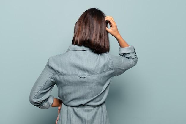 젊은 히스패닉계 여성이 우둔하고 혼란스러워하고 엉덩이에 손을 대고 머리에 다른 손으로 해결책을 생각하고, 후면보기