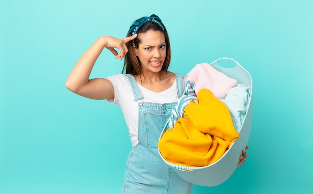 Молодая латиноамериканка смущена и озадачена, показывая, что вы сошли с ума, и стирает одежду