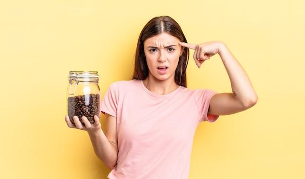 混乱して困惑している若いヒスパニック系女性は、あなたが正気でないことを示しています。コーヒー豆の概念