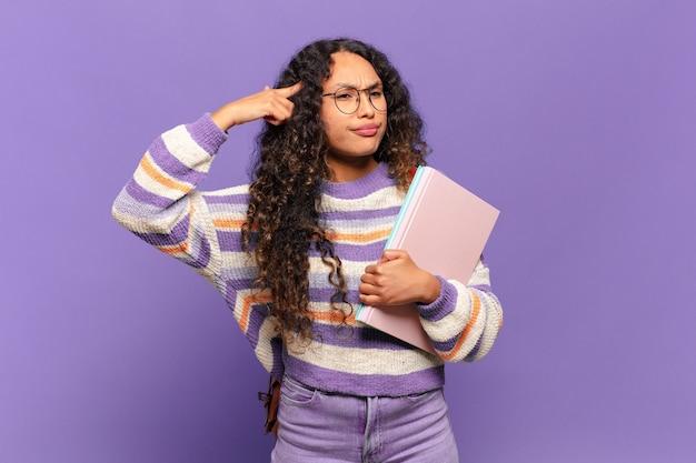 Молодая латиноамериканка смущена и озадачена, показывая, что вы сошли с ума, сошли с ума или сошли с ума. студенческая концепция