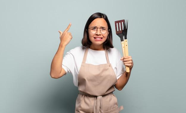混乱して困惑している若いヒスパニック系女性は、あなたが狂気であるか、狂っている、または頭がおかしいことを示しています