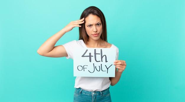 Молодая латиноамериканка смущена и озадачена, показывая, что вы сошли с ума. концепция дня независимости