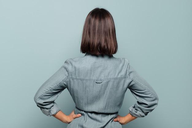 혼란 스럽거나 가득 차 있거나 의심과 질문을 느끼는 젊은 히스패닉계 여성, 엉덩이에 손, 후면보기