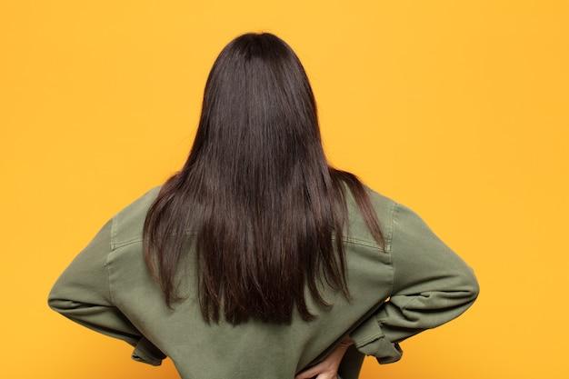 젊은 히스패닉계 여성이 혼란스럽거나 가득 차거나 의심과 질문을 하고 엉덩이에 손을 얹고 뒷모습을 보고 있습니다.
