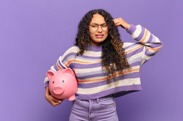Young hispanic woman feeling confused and puzzled, showing you are insane, crazy or out of your mind. piggy bank concept
