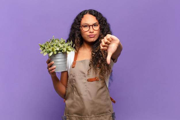 Молодая латиноамериканка чувствует себя сердитой, сердитой, раздраженной, разочарованной или недовольной, показывает палец вниз с серьезным взглядом. концепция садовника