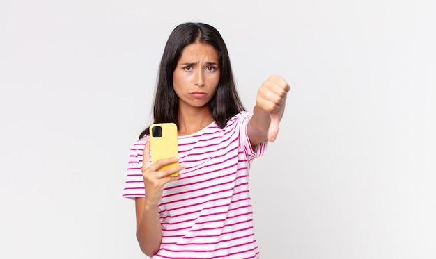 Молодая латиноамериканская женщина чувствует крест, показывает палец вниз и держит смартфон