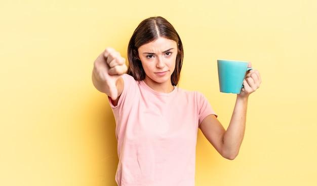 Молодая латиноамериканская женщина чувствует крест, показывает палец вниз. концепция чашки кофе