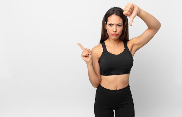 若いヒスパニック系の女性は、親指を下に見せて、十字架を感じています。フィットネスコンセプト