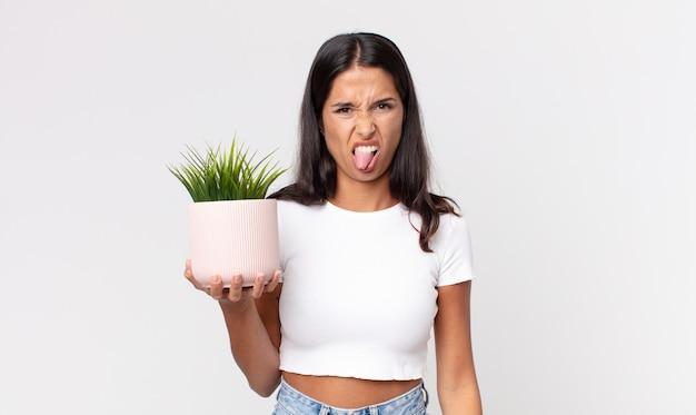 히스패닉계 젊은 여성은 역겹고 짜증이 나며 혀를 내밀고 장식용 식물을 들고 있다