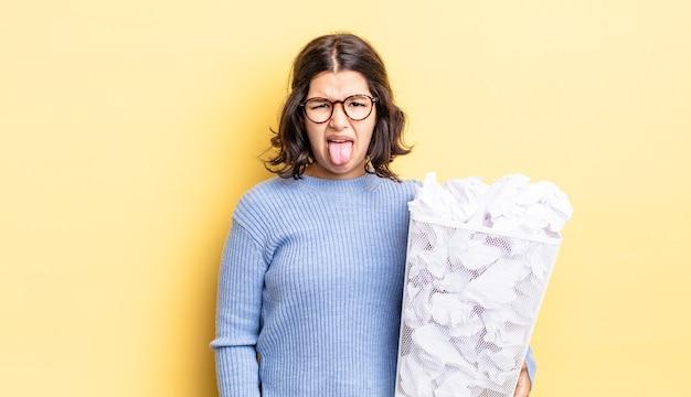 Молодая латиноамериканская женщина чувствует отвращение и раздражение и выкидывает язык за пределы концепции мусора