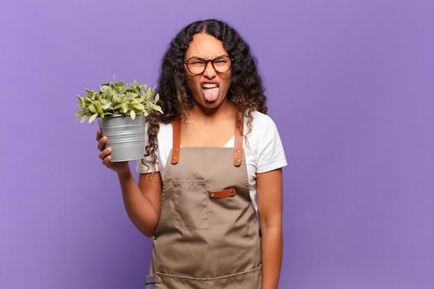 Молодая латиноамериканка чувствует отвращение и раздражение, высовывает язык, не любит что-то мерзкое и противное. концепция садовника
