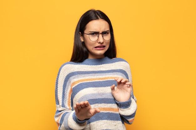 혐오감과 메스꺼움을 느끼는 젊은 히스패닉계 여성이 불쾌하거나 냄새가 나거나 악취가 나는 것에서 물러서 며 '웩'이라고 말합니다.