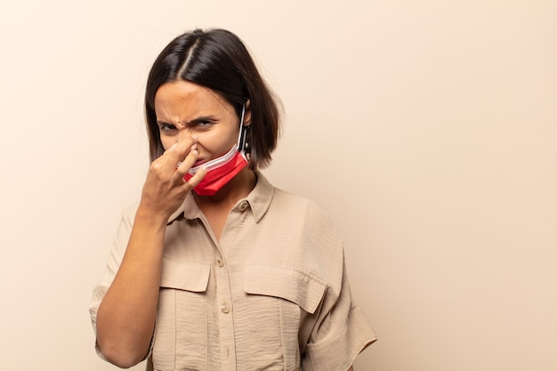 Young hispanic woman feeling disgusted, holding nose to avoid smelling a foul and unpleasant stench