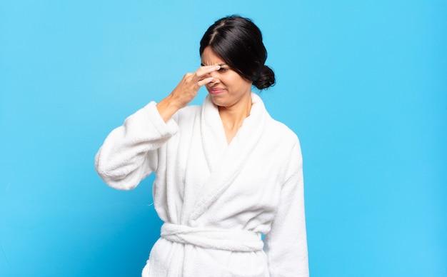 若いヒスパニック系女性は嫌悪感を感じ、悪臭や不快な悪臭を避けるために鼻を押さえています。バスローブのコンセプト