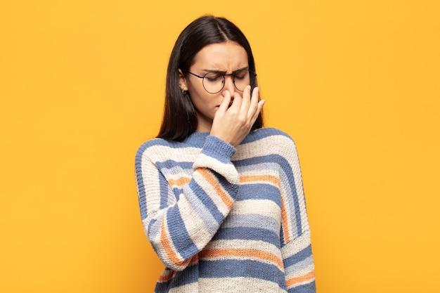 嫌悪感を感じ、悪臭や不快な悪臭を避けるために鼻を抱えている若いヒスパニック系女性