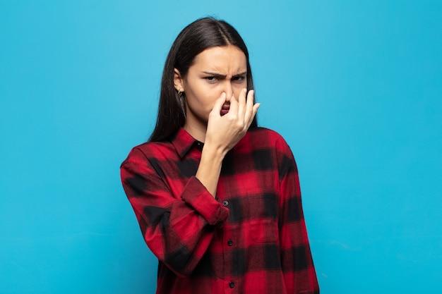 Молодая латиноамериканка чувствует отвращение, зажимая нос, чтобы не почувствовать неприятный запах
