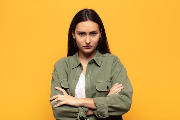 Молодая латиноамериканка чувствует недовольство и разочарование, выглядит серьезной, раздраженной и сердитой со скрещенными руками
