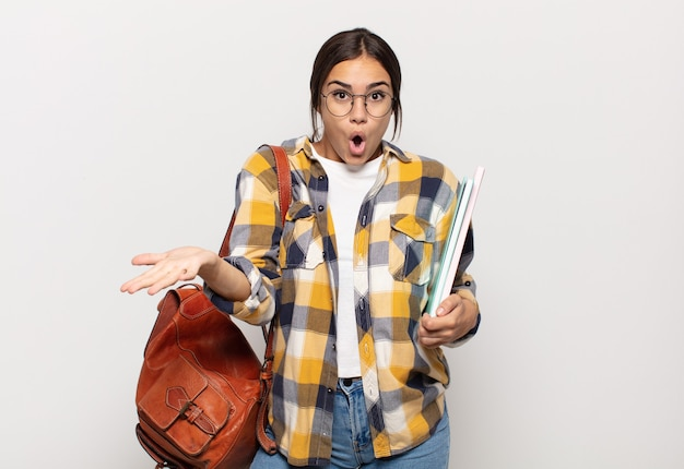 Молодая латиноамериканка чувствует себя чрезвычайно шокированной и удивленной, взволнованной и панической, с напряженным и испуганным взглядом