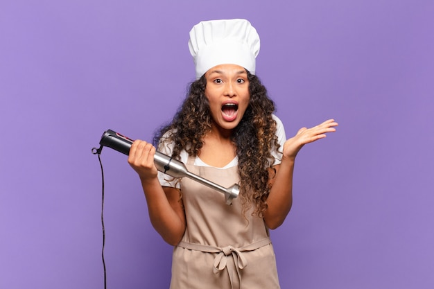 Young hispanic woman feeling extremely shocked and surprised, anxious and panicking, with a stressed and horrified look. chef concept