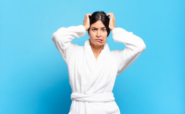 젊은 히스패닉 여성은 좌절감과 짜증이 나고, 실패에 지치고 지루하며 지루하고 지루한 작업에 지쳐 있습니다. 목욕 가운 개념