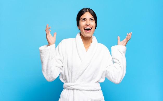 幸せ、驚き、幸運、驚きを感じ、両手を空中に上げて勝利を祝う若いヒスパニック系女性。バスローブのコンセプト