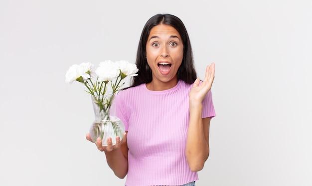 装飾的な花を持っている信じられないほどの何かに幸せと驚きを感じている若いヒスパニック系の女性