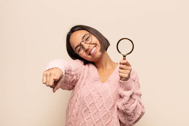 행복하고 자신감을 느끼는 젊은 히스패닉 여자, 양손으로 카메라를 가리키고 웃고, 당신을 선택