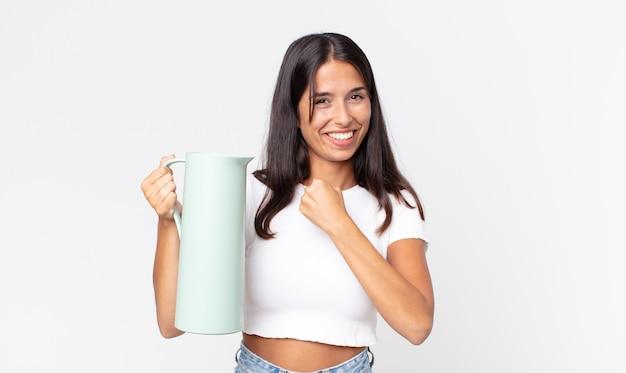 幸せを感じ、挑戦に直面している、またはコーヒー魔法瓶を祝って保持している若いヒスパニック系女性