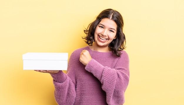 Молодая латиноамериканская женщина чувствует себя счастливой и сталкивается с проблемой или праздником. концепция пустой коробки