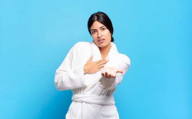 幸せで恋をしている若いヒスパニック系の女性は、片方の手が心臓の横に、もう片方の手が前に伸びて笑っています。バスローブのコンセプト