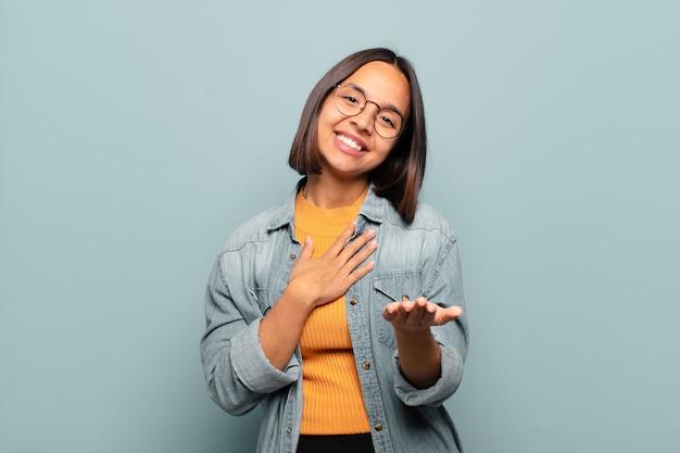幸せで恋をしている若いヒスパニック系女性は、片方の手が心臓の横に、もう片方の手が前に伸びて笑っています