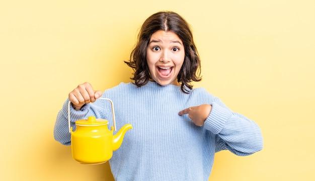 Молодая латиноамериканская женщина чувствует себя счастливой и с возбуждением указывает на себя. концепция чайника