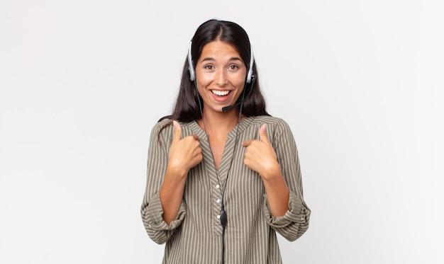 젊은 히스패닉계 여성이 행복하고 헤드셋으로 흥분한 채 자신을 가리키고 있습니다. 텔레마케팅 개념
