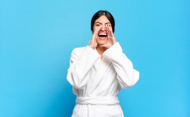 Молодая латиноамериканская женщина чувствует себя счастливой, взволнованной и позитивной, громко кричит, прижав руки ко рту. халат концепция