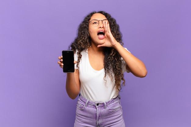 행복하고, 흥분되고 긍정적 인 느낌을주는 젊은 히스패닉계 여성이 입 옆에 손으로 큰 소리를 지르며 외칩니다. 스마트 폰 개념