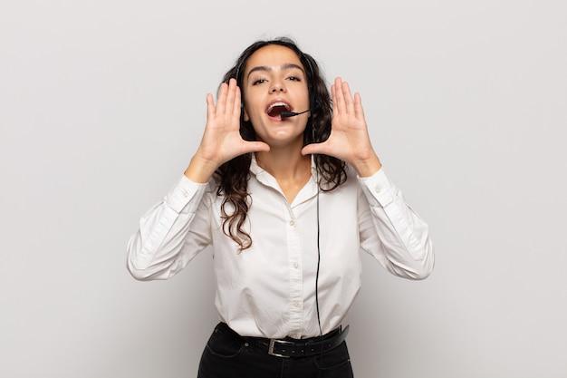 幸せ、興奮、前向きな気持ちで、口の横に手を置いて大きな叫び声を上げ、声をかける若いヒスパニック系女性