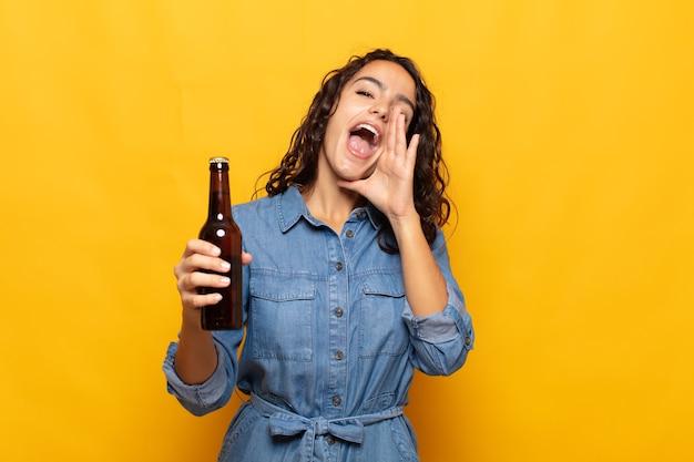 행복하고 흥분되고 긍정적 인 느낌을주는 젊은 히스패닉계 여성, 입 옆에 손으로 큰 소리를 지르고 외침