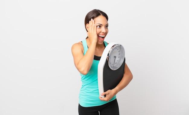 幸せ、興奮、驚きを感じ、体重計を持っている若いヒスパニック系女性