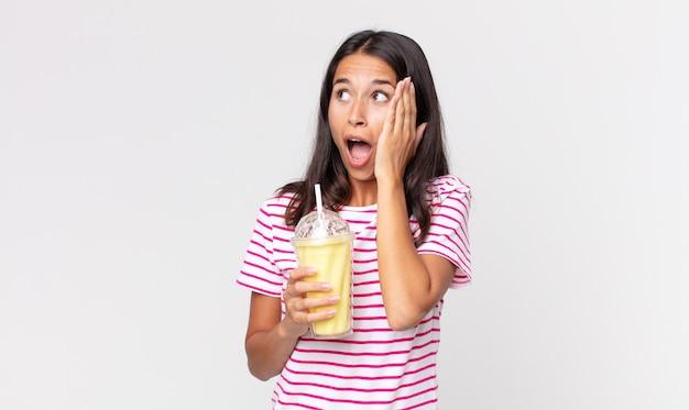 Молодая латиноамериканская женщина чувствует себя счастливой, взволнованной и удивленной и держит ванильный смузи молочный коктейль