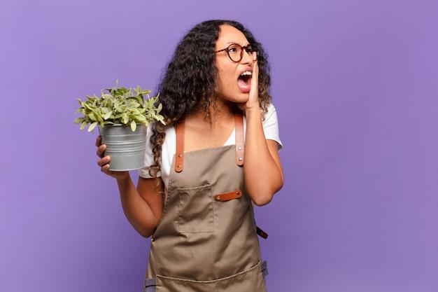 Молодая латиноамериканская женщина чувствует себя счастливой, взволнованной и удивленной, глядя в сторону обеими руками на лице. концепция садовника