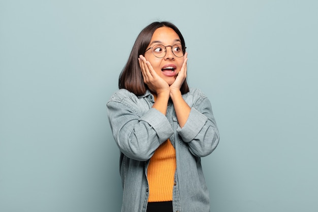 Young hispanic woman feeling happy, excited and surprised, looking to the side with both hands on face