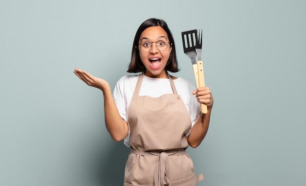 Молодая латиноамериканская женщина чувствует себя счастливой, взволнованной, удивленной или шокированной, улыбается и удивляется чему-то невероятному