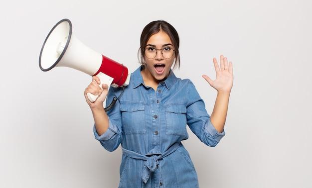 ヒスパニック系の若い女性は、信じられないほどの何かに幸せ、興奮、驚き、またはショックを受け、笑顔で驚いています