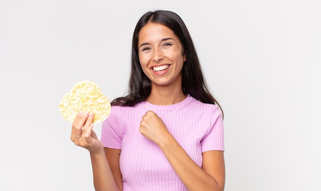 Young hispanic woman feeling happy and facing a challenge or celebrating and holding a rice cookie. diet concept